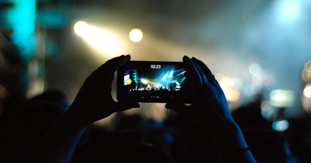 person holding cell phone up recording concert