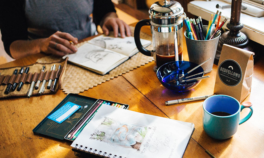 artists drawing on a table at a coffee shop