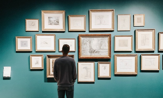 man looking and multiple framed artworks on a teal wall